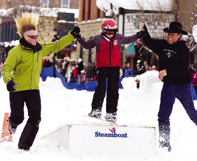 Skiing icon Glen Plake, left, and Scott Flower, right, help Cole Puckett, over the jump ramp on Lincoln Avenue during Winter Carnival last year.