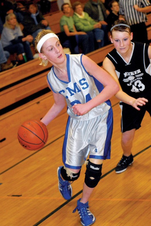 Craig Middle School eighth-grader Bailey Hellander drives past a player from visiting Meeker High School on Saturday. The Bulldogs won the matchup, 35-25, against the Cowboys.