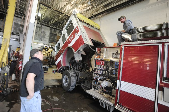 City of Steamboat Springs Public Works head mechanic Jason Weber, left, talks to mechanic Sam Wisecup on Thursday about repairs to a fire engine at the department's shop. The city is proposing adding 1,200 square feet of office space and equipment storage areas to the building.
