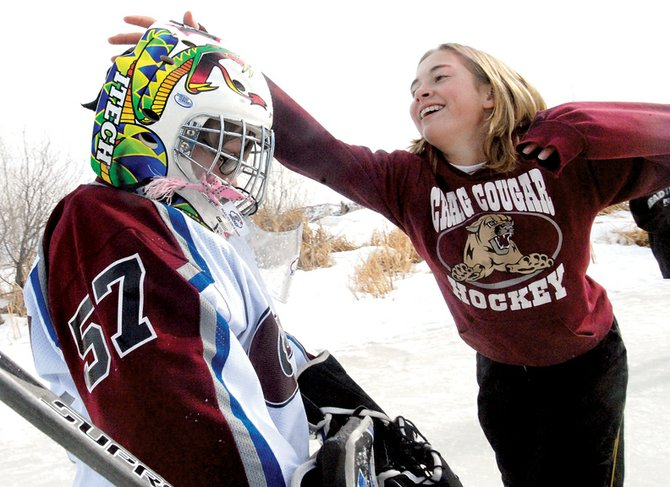 Ripley Bellio, right, gets ready to tackle Riley O'Leary on the ice during a hockey game Saturday at Yampa River State Park's Full Moon Ski and Skate Open House. Warm temperatures didn't stop many from coming out to enjoy the park in the annual event.