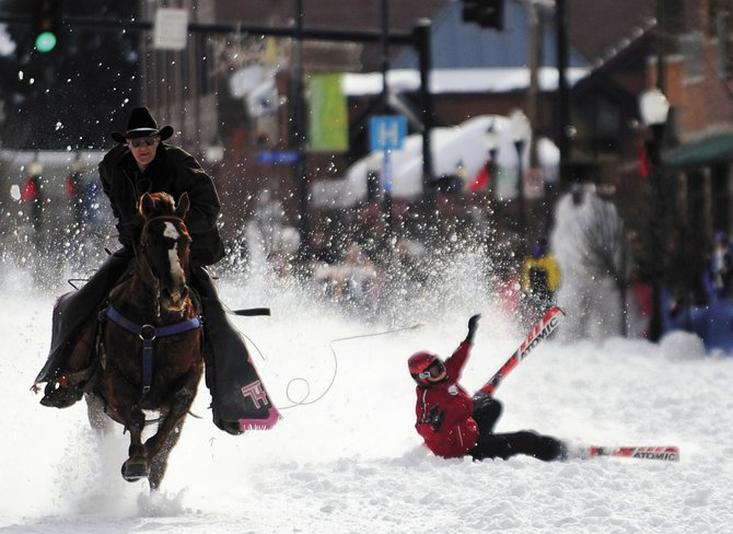 Steamboat Springs 9-year-old Katherine Harnick crashes during the Winter Carnival street events skijoring competition Saturday. She was being pulled by North Routt rancher Guy Urie.