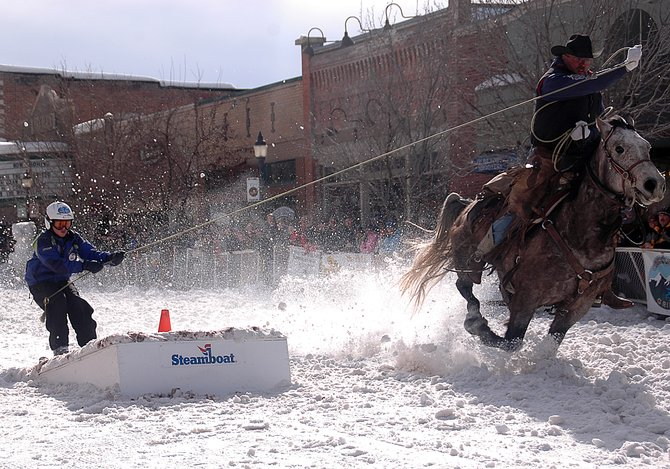 Cowboy Doug Wheeler gives Tanner Visnick one extra tug as Visnick prepares to fly over a jump on Lincoln Avenue on Sunday in Steamboat Springs. The city's annual Winter Carnival wrapped up Sunday.