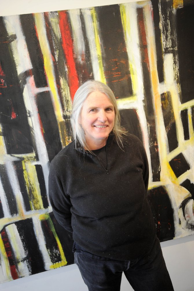 "Laura Wait stands in front of one of her favorite acrylic on canvas pieces named ""The Knights Blacksmith Anticipate a Crusade."" Her work is on display at the K. Saari Gallery in downtown Steamboat Springs."