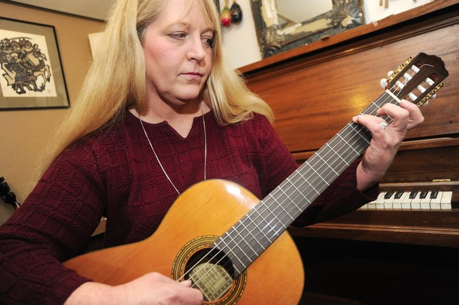 "Stagecoach resident Heather Anne Ross plays a guitar Wednesday at First String Music. She recently released her debut CD, ""Walkin' Till You Fly."""