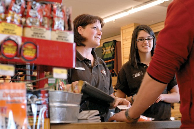 Buffi Harrington, left, and Megan Trujillo ring up a customer at Murdoch's Ranch & Home Supply on Thursday. Sales across the county were higher than expected in December 2008, and local government officials said they were pleased to see the corresponding increase in sales tax revenue.