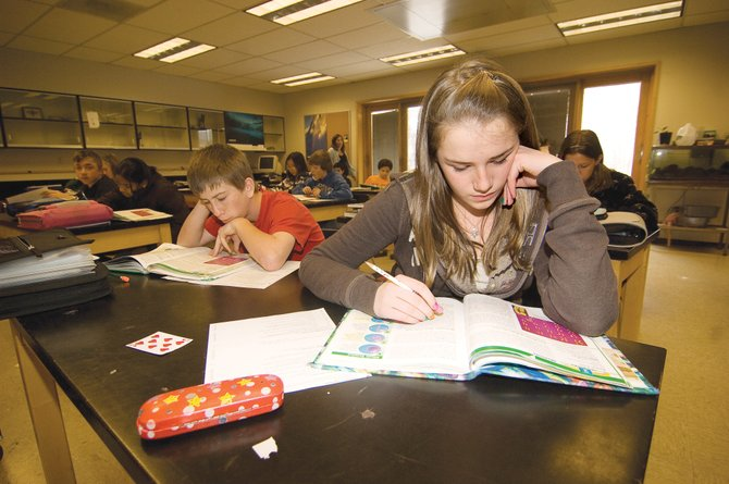 Seventh-grader Ashley Spitellie, front, and classmate Dillon Kidder read a section in their science books during class at Steamboat Springs Middle School on Monday. The Steamboat Springs School Board discussed class size at its meeting Monday night and voted, 3-2, to keep the policy under the control of the superintendent.