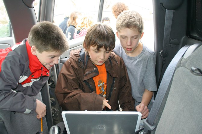 Students in Robin Bush's sixth-grade class in Hayden gather around the computer of Tim Lim, an engineer with the National Center for Atmospheric Research, minutes after releasing a weather balloon. The balloon was transmitting data about pressure, temperature, wind speed and location back to Lim's computer.