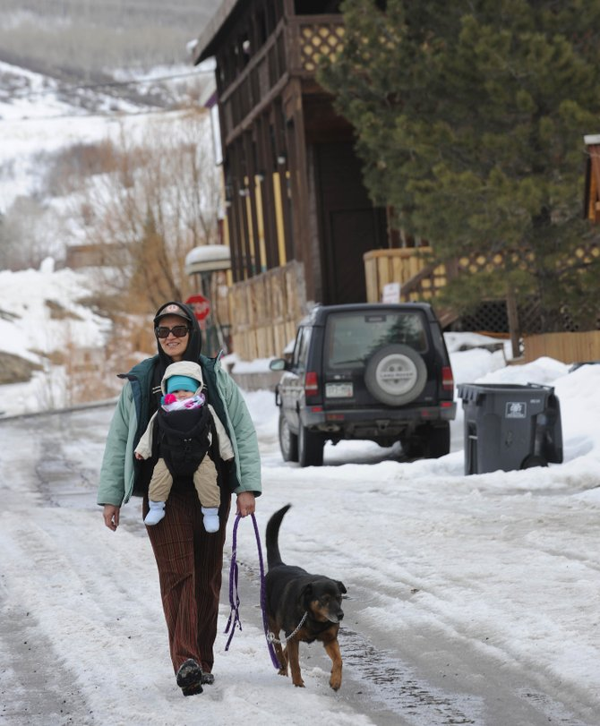 Oak Creek resident Gulya Paraketsova walks her dog, Ruby, with her grandson, Andrey, on Wednesday on West Colfax Street in Oak Creek. Three quarters of respondents to a recent Oak Creek policing survey said code enforcement such as leash laws and parking is an important need in town.