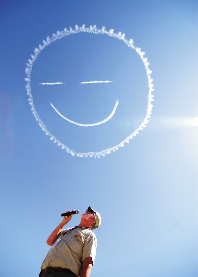 Wild West Air Fest emcee Mike Forney looks up at a smiley face written in the sky by skywriter Steve Oliver above Steamboat Springs Airport in August 2008. The photo, taken by Matt Stensland, was one of several Steamboat Pilot & Today images that earned a Colorado Associated Press Editors and Reporters award at a ceremony Friday night in Denver.