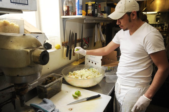 Cantina Mexican Restaurant cook Sergio Esquivel squeezes lime onto a Mexican salad Friday afternoon in the restaurant's kitchen. Cantina owner Kristi Brown says business has been down compared to last year, but she is optimistic about business for the rest of the ski season.