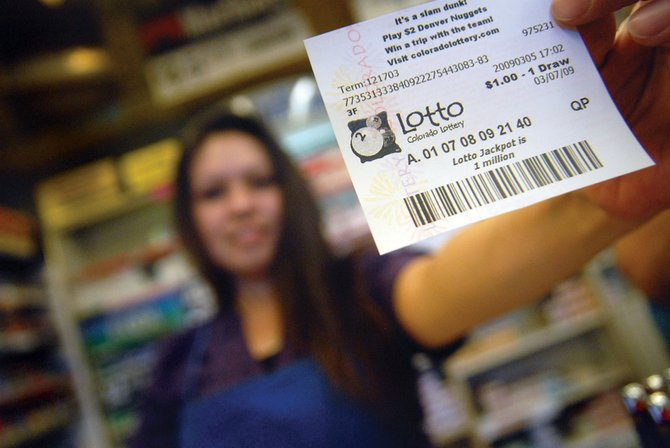 Rose Fief, who works as a clerk at Smoker Friendly at 40 E. Victory Way, hands a Colorado Lotto ticket to a waiting customer Thursday afternoon. Sometime earlier in the week, she did the same thing for another customer, and it turned out to be worth $1.17 million. Smoker Friendly will get a $5,000 bonus for selling the winning ticket.