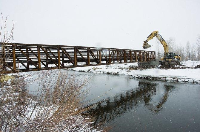 A trackhoe, operated by Duckels Construction, lifts the new footbridge into place Thursday over the Yampa River at the Chuck Lewis State Wildlife Area. The bridge provides access to a 50-acre lake containing northern pike.