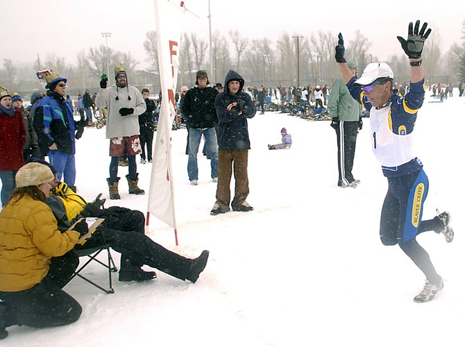 Mike Kloser, of Vail, raises his arms in victory as he crosses the finish line for his 10th Steamboat Pentathlon championship Saturday. Kloser has won more than half of the 18 pentathlons and finished with a five-minute lead on Barkley Robinson.