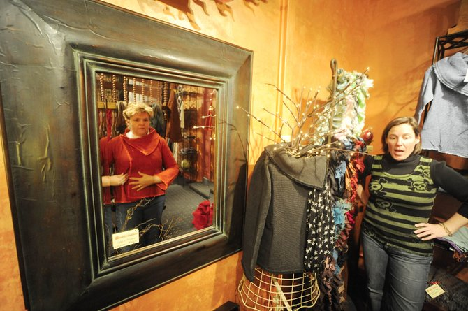 Embellishments owner Ashley Edinburg talks to customer Annette Aulick, of Scotts Bluff, Neb., while she tries on a Nepalese jacket Saturday at the store located at 114 Eighth Street. Edinburg's landlord, Steve Nelson, has decided to cut her rent to help her through tough economic times.