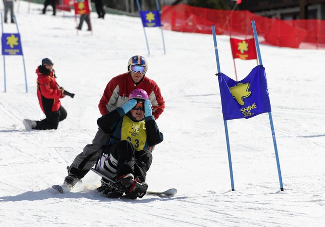 Katelyn Treesh, 15, of Indiana, covers her eyes as she skis down a slalom course with Steamboat Ski Area instructor Derrick Charpentier on Friday. Katelyn was one of 24 children who participated in The Sunshine Kids program, which serves children with cancer.