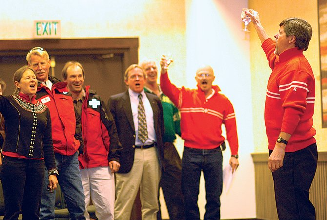 Gregg Tipton leads current and former members of the Steamboat Ski Patrol in a tribute to John Fetcher on Sunday at Fetcher's memorial service at the Sheraton Steamboat Resort.