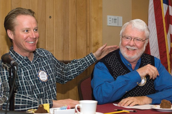 Rotarian Jamie Morgan, left, congratulates teammate and fellow Rotary Club member Mike Forney during a exhibition Knowledge Bowl meet at Tuesday's luncheon. The Rotarians, who are giving $500 to the Knowledge Bowl Team for the state meet, invited the members of the Steamboat team to lunch.