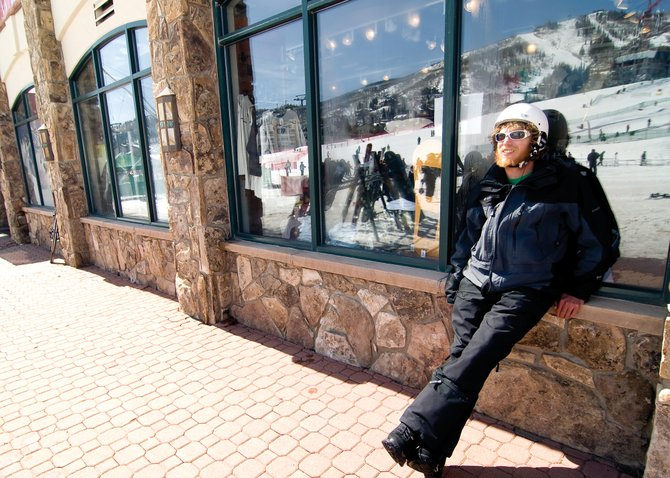 Snowboarder Matt Currey hangs out in the sun at Steamboat Ski Area on Thursday afternoon. Ski area officials expect business to remain solid for the next couple of weeks with a slight drop during the final week.