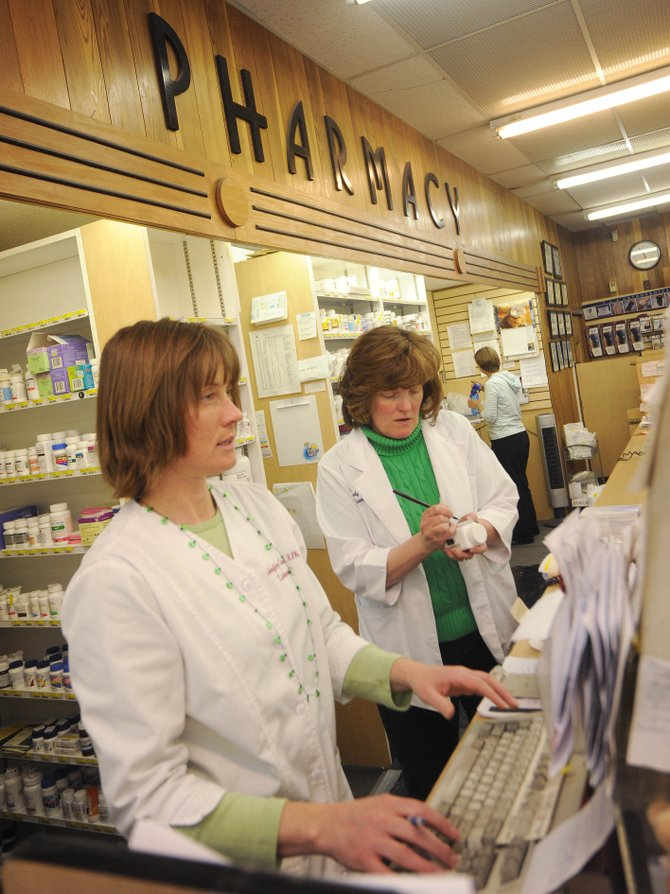 Lyon&#39;s Corner Drug pharmacists Jennifer Campbell, left, and Wendy Lyon, work Tuesday afternoon in the pharmacy. Police say a man broke into the pharmacy Monday night and attempted to take painkillers.