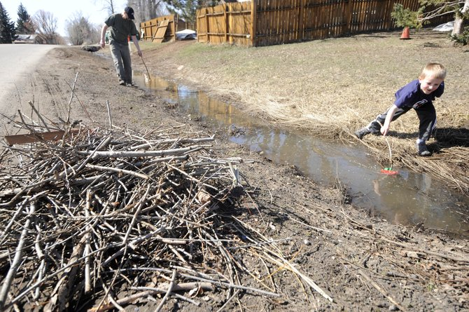 Brick Dalsis plays with a toy boat with his father Greg after the two finished clearing twigs from a ditch Wednesday in front of their home on East Maple Street. The city of Steamboat Springs will no longer provide scoria and spring debris removal for residents and businesses who employ private landscape contractors.