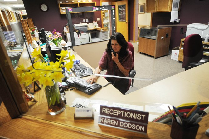 Karen Dodson transfers a call Thursday while filling in as receptionist at City Hall. Starting on April 3rd, Centennial Hall and City Hall may be closed Fridays as part of a furlough program.