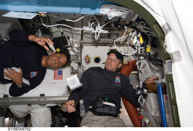 Astronauts Joseph Acaba, left, and Steve Swanson, both mission specialists, are pictured near the robotic workstation in Destiny, the U.S. laboratory, within 24 hours of beginning their mission&#39;s second spacewalk, which they completed Saturday.