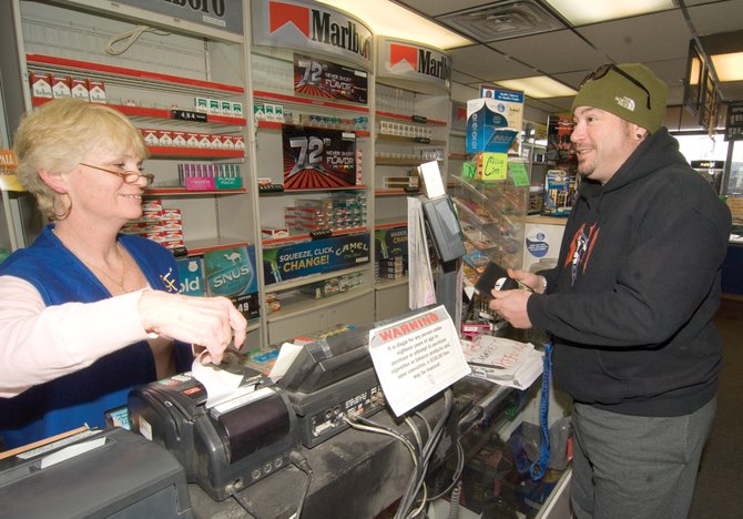 Store manager Barbara Chapman-Baker jokes with customer Rod Story who was at the Smoker Friendly Central Park Plaza store to pick up some cigarettes. A federal tax increase, which goes into effect Wednesday, will bring the excise tax on a pack of cigarettes from 39 cents to $1.01