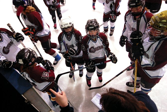 Craig Cougars' Kaylee Durham, left, and Emma Samuelson listen to direction Saturday from coach Tanya Ferguson before their game against visiting Grand Junction. It was the first home game for the Craig Cougars, a U-16 girls hockey team, who fell to Grand Junction, 4-1, and, 3-2, in a doubleheader.