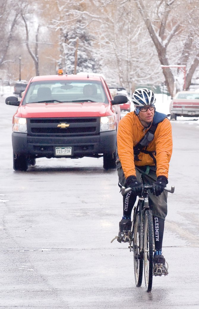 Cyclist Matt Pronovost didn't let the wet weather, or traffic, stop him from rolling along Yampa Street on Monday morning. Pronovost says he commutes to and from work year-round. A bill currently being debated in the Colorado General Assembly would change the way cyclists interact with motor vehicles.
