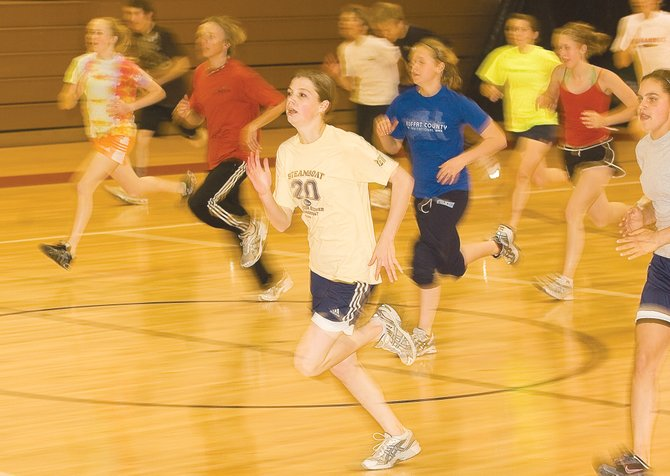 Runner Kimberly Heald and the other members of the Steamboat Springs High School track team warm up inside the old gym Wednesday afternoon. The track team does its best to get outside, but there are times when the weather forces the runners and throwers to work out inside the school.