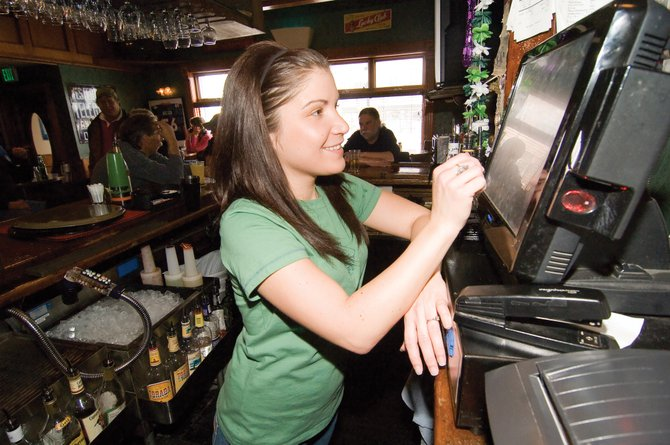 Bartender Megan Mathews punches in a drink order at the Old Town Pub in downtown Steamboat Springs. Like most in the restaurant business, Matthews enjoys the benefit of free or discounted shift meals. A bill sponsored in the state Legislature by Sen. Al White, R-Hayden, aims to protect the meals from taxation by the Colorado Department of Revenue.