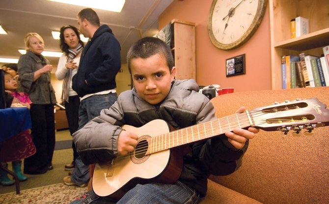 Hector Jacobo Dominguez plays guitar at a social gathering for students in the college's English as a Second Language program. Program director Jen leRoux visits with students Maria Bonilla and Rigoberto Bonilla in the background.