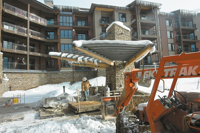 Construction crews at Trailhead Lodge continue working on outdoor amenities, such as stone slabs for the community barbecues, while furniture is moved into the condominiums.