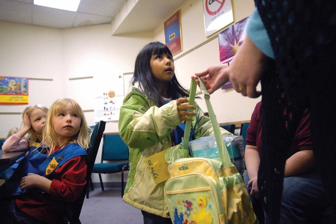 Daisy Troop 3557 member Rebecca Cruz, middle, hands her pack of gifts Thursday to RaeAnne Durham, of Moffat County Social Services. The gifts, bought as part of a troop customer service project, will be used for incoming foster children in Moffat County.