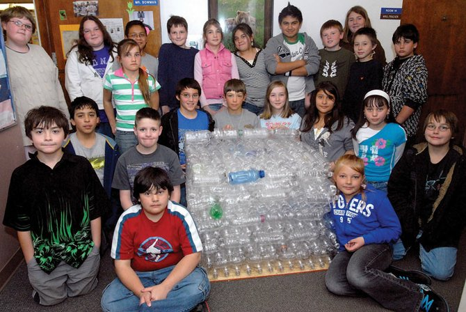 George Bowman's fifth-grade class is collecting plastic bottles and assembling them into a cube to illustrate how much trash is left behind. The class intends to display the sculpture, which isn't finished as of yet, around town.