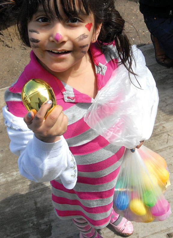 Sam Cancino, 4, holds the golden egg she found Sunday afternoon at Sandrock Ridge Care & Rehab, 943 W. Eighth St., during an Easter egg hunt. Scattered among more than 1,000 Easter eggs were six gold and silver eggs that contained gift cards.