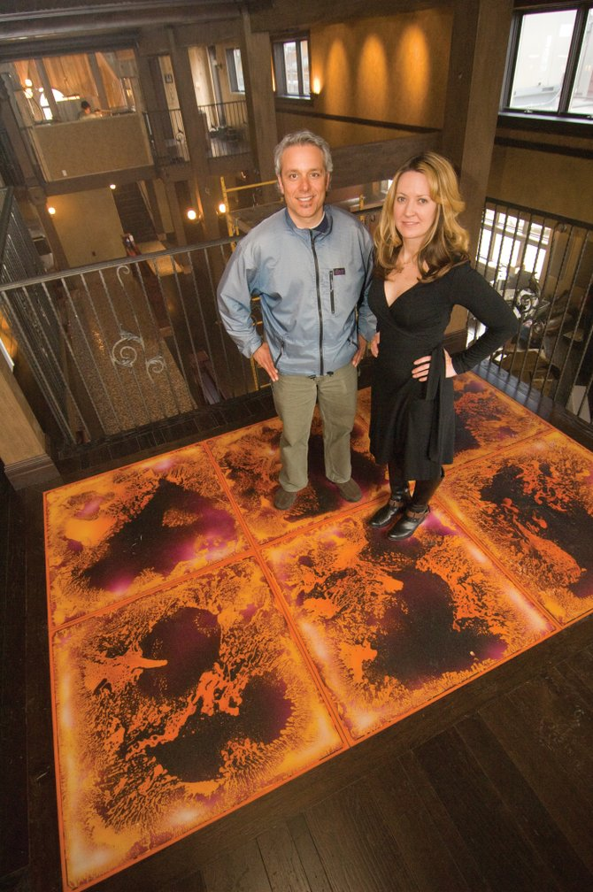 Managers Joey Rind and Amy Garris stand on a floor, which changes colors and design when stepped on, located on the second level of the Ghost Ranch Saloon. The venue is nearly complete, and the managers are excited about the establishment's planned opening in May.