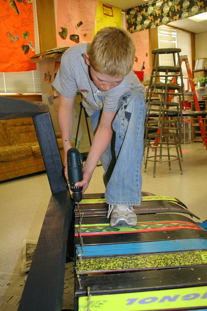 Sixth-grader Dusty Earle screws in some of the 30 pieces of skis used by the Partners in Routt County after-school group to construct a bench at Hayden Middle School.