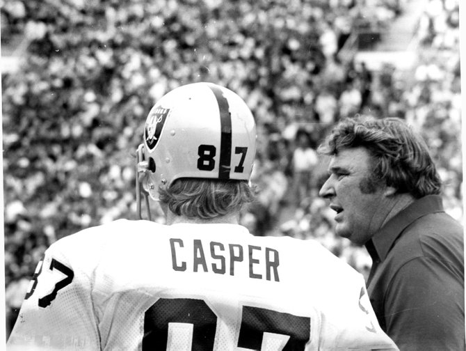 Future hall-of-famers Dave Casper and John Madden, of the Oakland Raiders, confer on the sidelines during a game played against the Green Bay Packers in Lambeau Field on Sept. 17, 1978.
