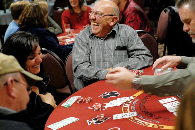 Dave Cole, middle, shares a laugh with Janae Shelton and other blackjack players Friday at Casino Night at the Holiday Inn of Craig, hosted by Horizons Specialized Services. The event, Horizon's biggest fundraiser of the year, pays for services in Moffat County, including development programs for children ages 3 and younger, adult day programs and others.