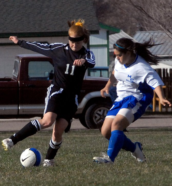 Moffat County's Ana Maria Flores, right, defends Battle Mountain's Haille Hogfeldt during the second half of the teams' game Monday at Woodbury Park. The Huskies won, 5-1.