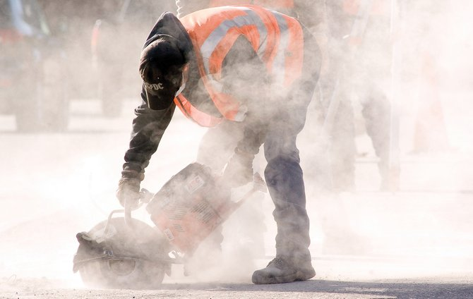 Steamboat Springs city worker Levi Wisecup uses a powerful saw to cut the sidewalk near Third Street and Lincoln Avenue on Monday. The city is considering cuts to its capital improvement budget that could limit projects this summer.