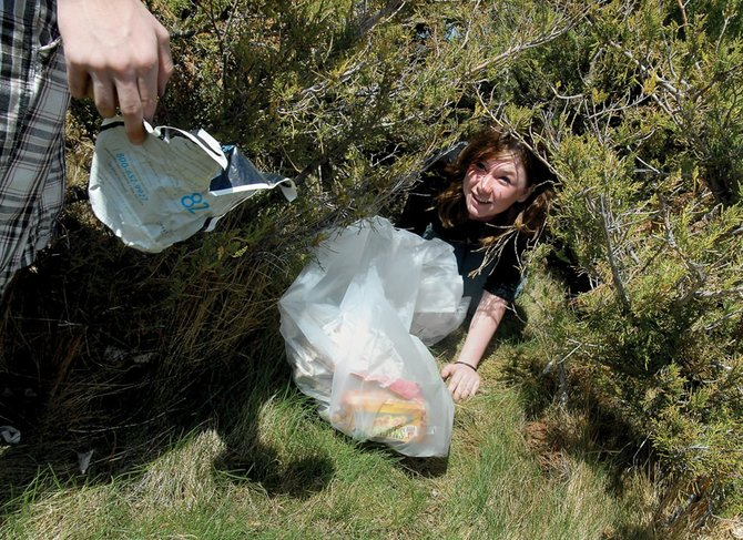 Satori Weis, 14, a Moffat County High School freshman, climbs out of a bush Tuesday during an Earth Day cleanup. More than 500 students picked up trash throughout the day at MCHS and surrounding properties.