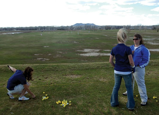Nike Cleverly, left, tees up Tuesday while Callie Papoulas talks with coach Ann Marie Roberts about her tee shot during practice at Yampa Valley Golf Course. The Moffat County High School girls golf team competed Monday at the Rifle Creek Golf Course, finishing fourth out of seven teams.