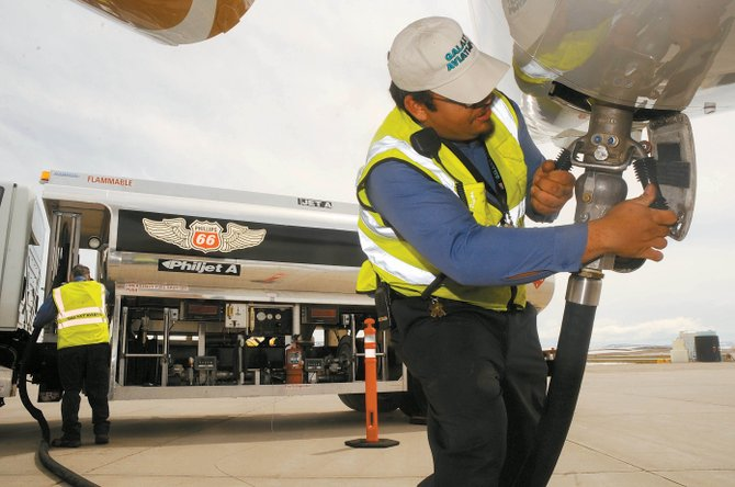 Olin Clark, head lineman for Galaxy Aviation, attaches a fuel hose to a jet Friday at Yampa Valley Regional Airport. Town officials say the state of Colorado has not given the town its share of sales tax revenues from fuel sales at the airport.