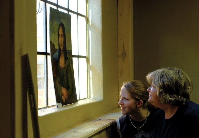Delina Miller, left, and her mother, Barbara Miller, look at a painting Wednesday created by Alicia Nelson at the Moffat County High School senior art show. Delina, who displayed her work in the show as well, was among 10 students who used different media types to create artwork for the event.