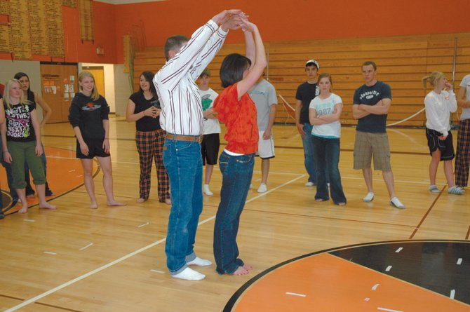 Ty and Gina Zabel demonstrate a swing dance move for Hayden High School students at a dance clinic Thursday. The students learned swing, waltz and two-step techniques to use at the school's prom Saturday.