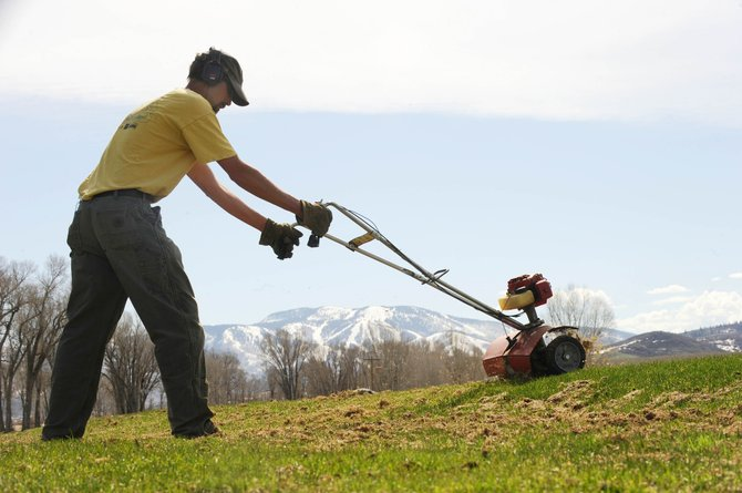 Steamboat Golf Club superintendent Andy Keyek uses a dethatcher to remove dead grass from the course Wednesday morning. The course opens Saturday. &quot;It came out of winter alright,&quot; Keyek said about the course.