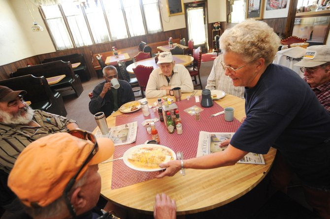 Waitress Susan Cardenas serves breakfast to Dinty Moore's Family Restaurant regulars, clockwise from left, Chuck Klesath, Eugene Germain, Chris Neil, John Maynarich, Bob Johnson and Pete Koler on Thursday morning in Oak Creek. The restaurant closed Saturday. A new restaurant called The Oak will open in its place.