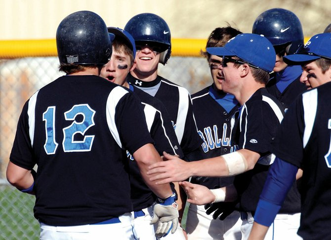Teammates congratulate Moffat County High School senior Erik Leonard after cranking out a 3-run home run Tuesday against visiting Rifle at Craig Middle School. The Bulldogs failed to topple the Bears however losing 9-4 and 11-6.